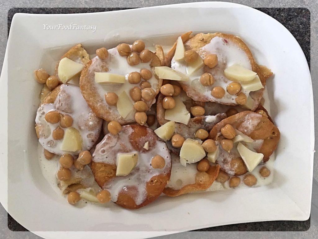 Layering papdi, yogurt, potato, chickpeas for papdi chaat