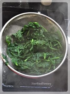 Draining water from boiled spinach for palak paneer
